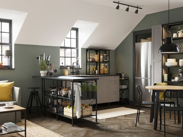 An anthracite/grey corner kitchen, a black bar stool, a black trolley, a striped rug and black containers with fresh herbs.