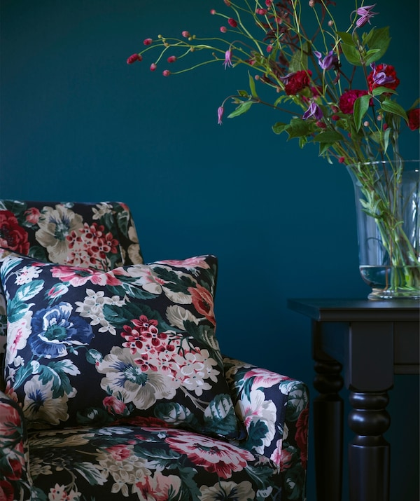 An arm chair with matching cushion in a bold floral pattern.