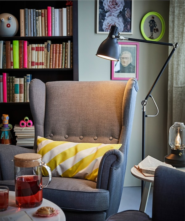 An armchair and cushion illuminated with an IKEA ARÖD floor lamp.