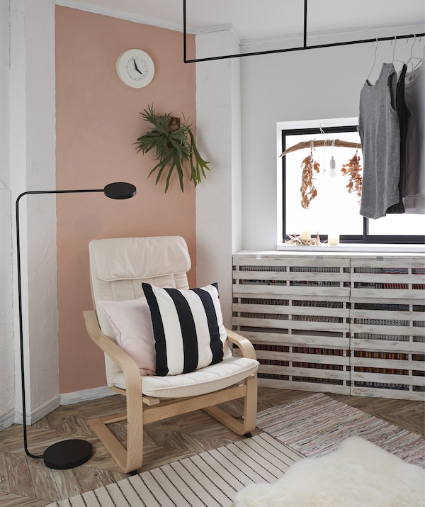 An armchair and floor lamp in the corner of a room with a pink feature wall and clothes hanging on a rail across the window.