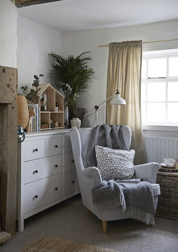 An armchair with throw, cushion and lamp next to a large white chest of drawers.