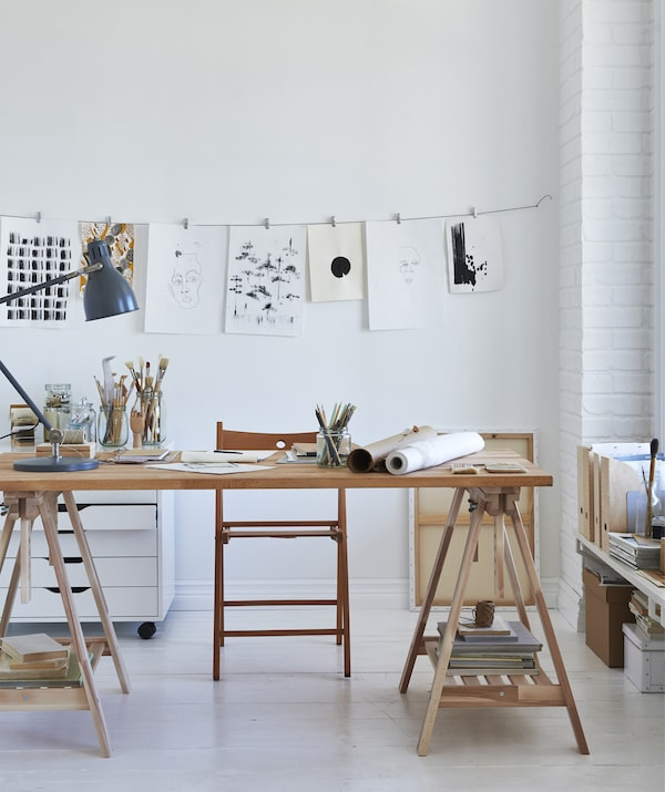 An artist's wooden desktop on trestles with a display of drawings hanging from a wire on the wall.