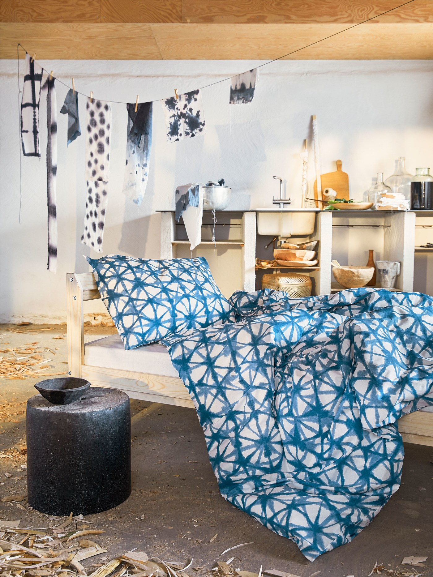 An artsy bedroom, with a bed dressed with a blue-on-white STJÄRNFLOCKA quilt cover that resembles a Japanese dyeing technique.