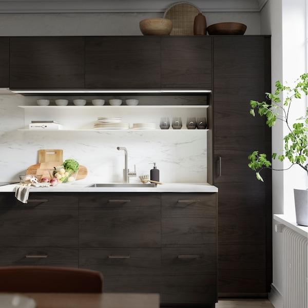 An ASKERSUND kitchen in dark brown ash design with chopping boards and vegetables on an EKBACKEN worktop in marble design.