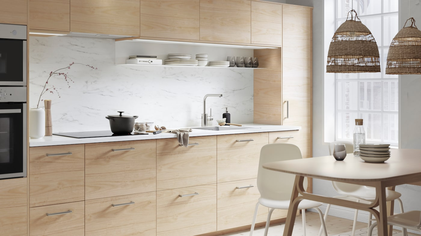 An ASKERSUND kitchen in light-ash effect with an EKBACKEN worktop in white marble effect. There is a casserole on the hob.