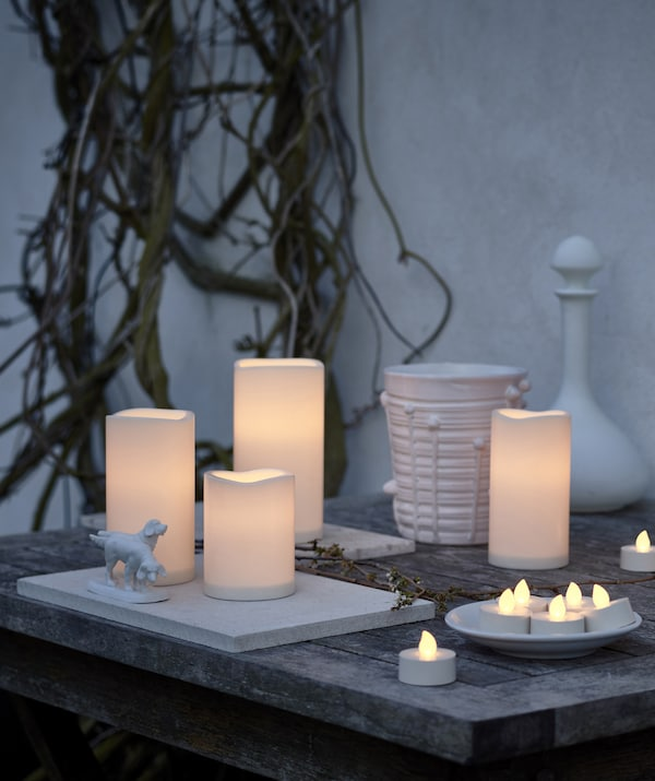 An assortment of LED candles gathered together outside on a wooden table, against a white wall.
