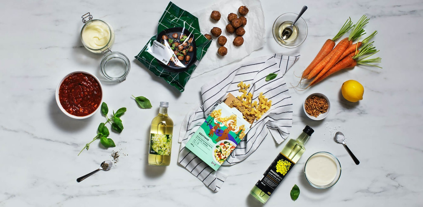 An assortment of plant based ingredients arranged around a package of plant balls and a bottle of cooking oil.