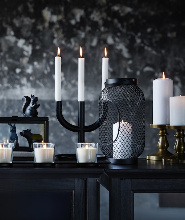An assortment of white candles and candle holders on a black table, against a mottled black and grey wall.