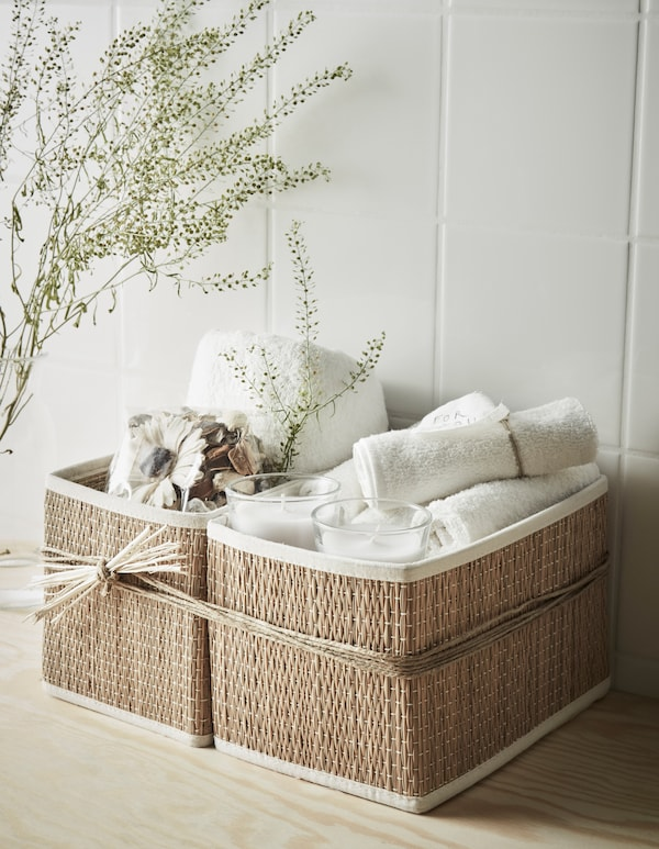 An at-home spa gift basket with washcloths, scented candles, potpourri and a towel.