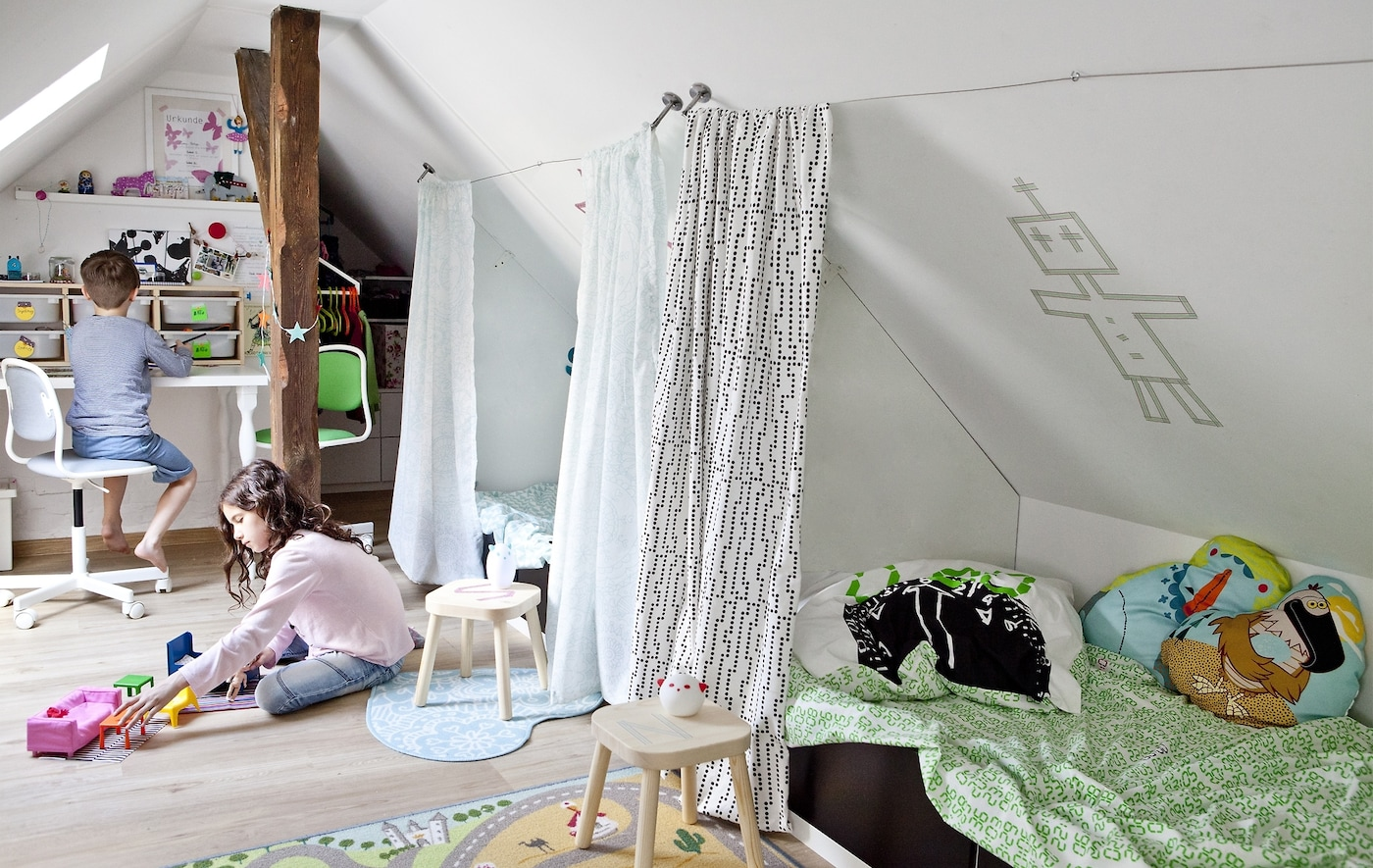 An attic bedroom with two beds and two children playing