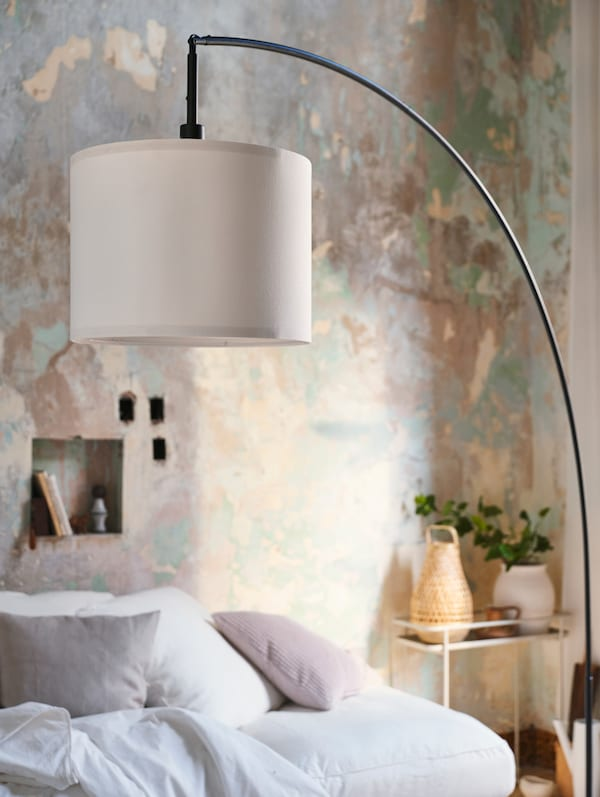 An black arched floor lamp base with a white lampshade. There is a cream colored plant stand in the background.