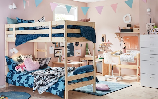 An den rosafarbenen Wänden dieses Kinderzimmers hängen viele selbst gemalte Bilder und Zeichnungen. Mit funktionellen Kieferholzmöbeln, die beim Organisieren der Malutensilien helfen, wird die Fantasie noch weiter beflügelt. In diesem Zimmer ist u. a. auch MYDAL Etagenbettgestell aus Kiefer zu sehen