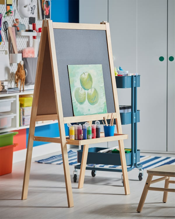 An easel in softwood that has an included tray where paint in different colours stands.
