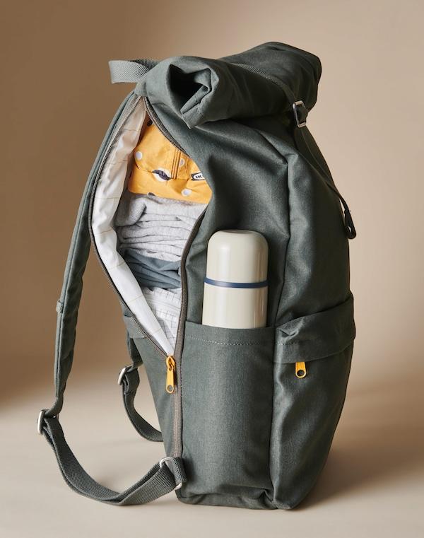 An einem olivgrünen Rucksack ist eine Seite geöffnet. Darin sind Kleidung, RENSARE Taschen und eine HÄLSA Stahlisolierflasche zu sehen.