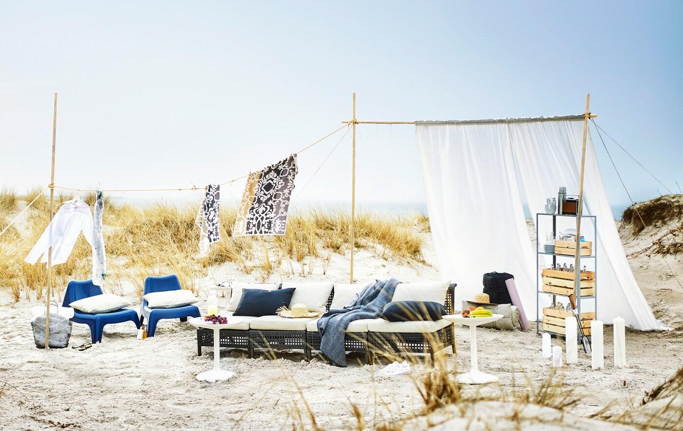 An einem Sandstrand sind ein Sofa, blaue Strandstühle, ein Regal, eine Wäscheleine & ein wehender weißer Vorhang platziert.