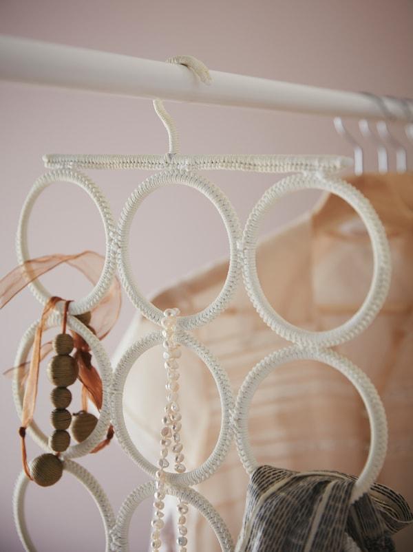 An einer Kleiderstange hängt ein KOMPLEMENT Aufhänger mit Schals, Ketten und anderen Accessoires.