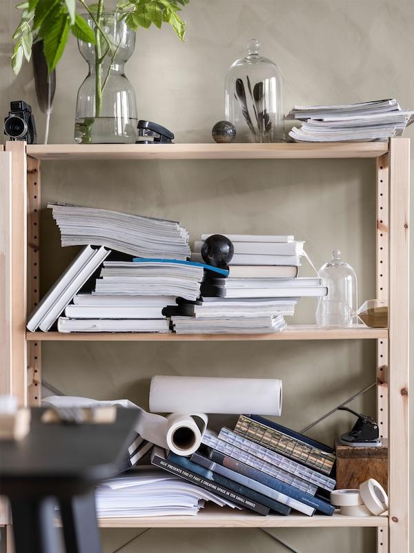 An einer Wand steht ein Holzregal mit chaotischen Stapeln aus Büchern und Zeitschriften und Glasvasen mit grünen Stängeln und Federn.