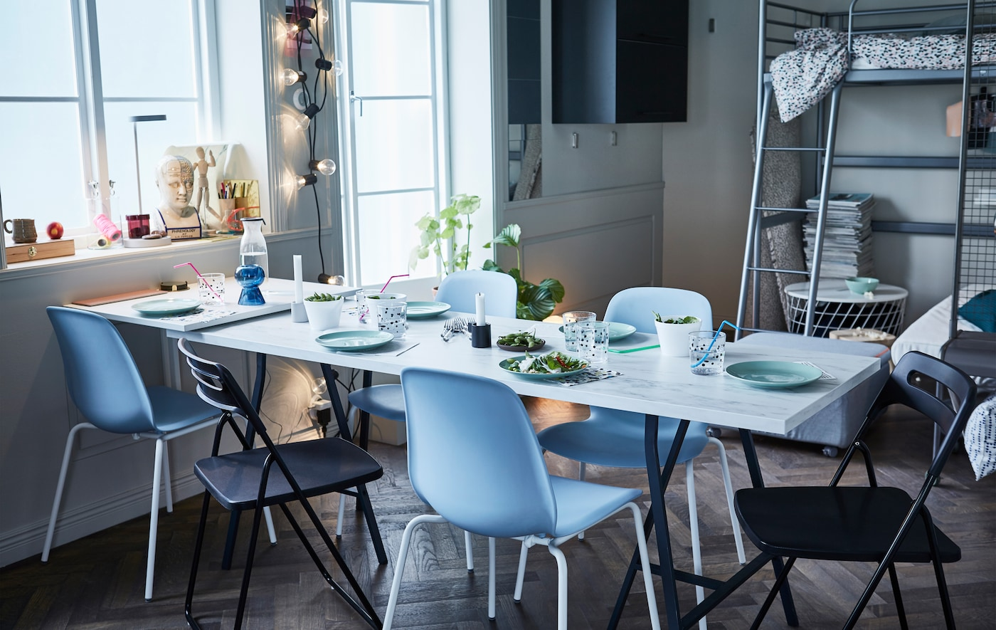 An EKBACKEN work top with white marble effect used as a pop-up table top surrounded by stackable and foldable chairs.