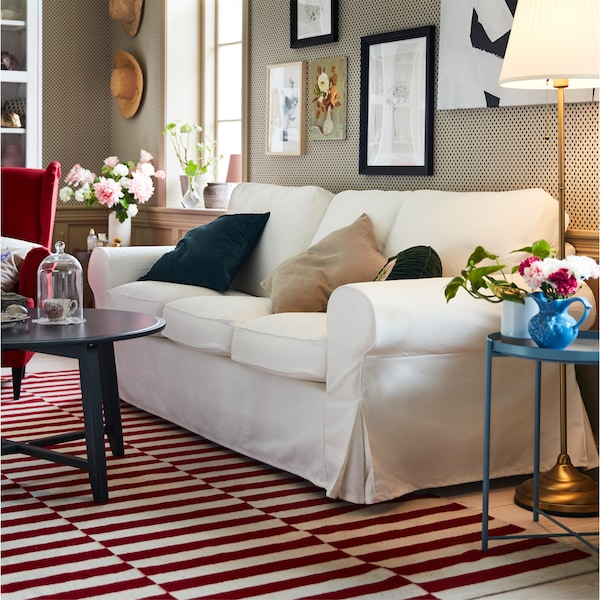 An EKTORP three-seat sofa in white is standing on a red and white rug in a living room that has a traditional look.