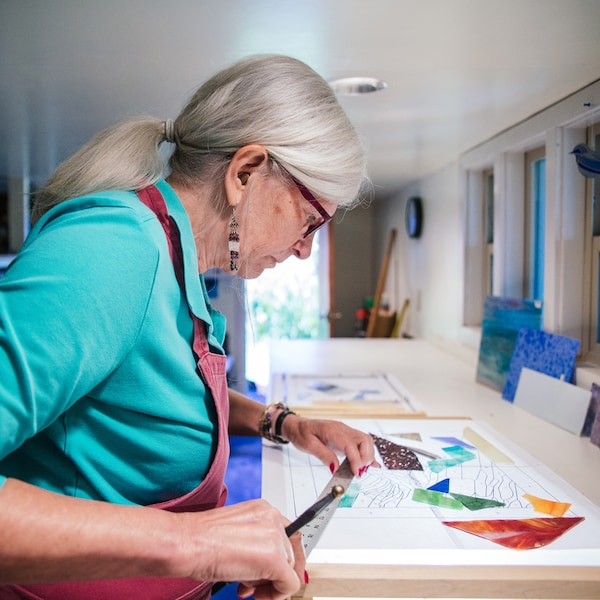 An elderly woman wearing an apron is holding a metal ruler, concentrating on the piece of art in front of her.