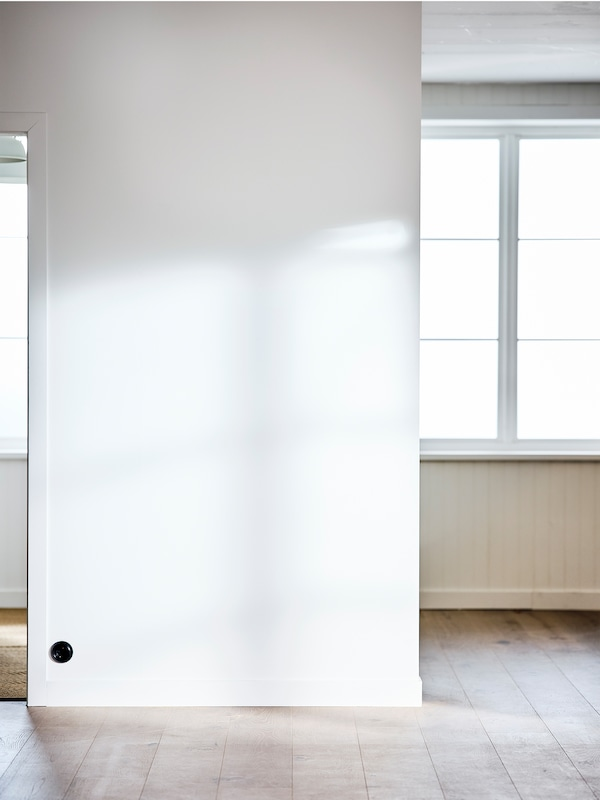 An empty room with a big window, white-painted walls and white-stained floorboards.