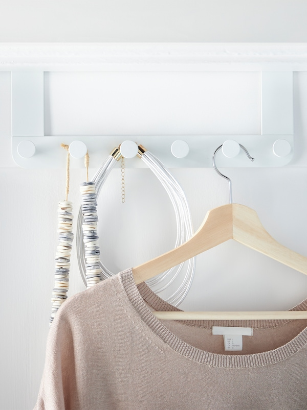 An ENUDDEN hanger in place over the top of a door, accessories and a top on a hanger hanging on its row of knobs.