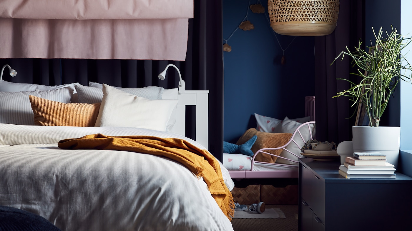 An extendable bed by a white bed with beige/white bed linen, a dark beige cushion, pink curtains and a bamboo pendant lamp.