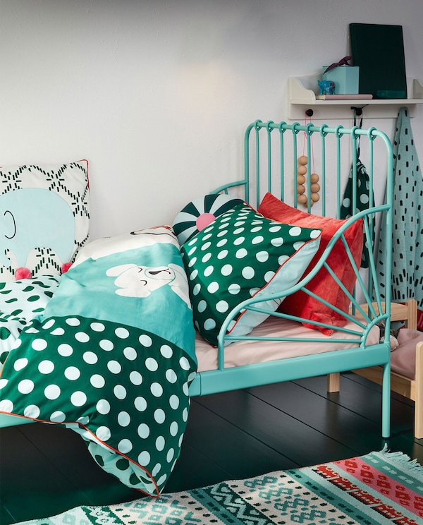 An extendable bed frame in turquoise and KÄPPHÄST bed linen in a patchwork/toys pattern in turquoise, blue and white colours.