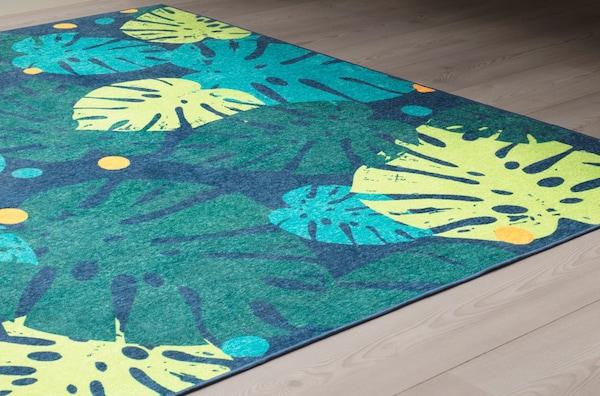 An green, URSKOG rug with a leaf pattern.