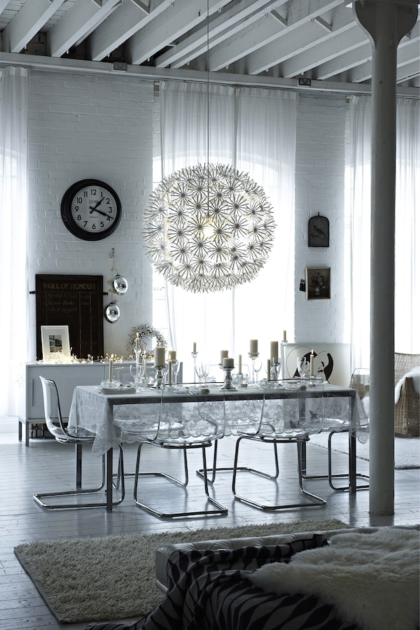 An icy cool glass-effect dining room with a snowball lampshade and a large white rug.
