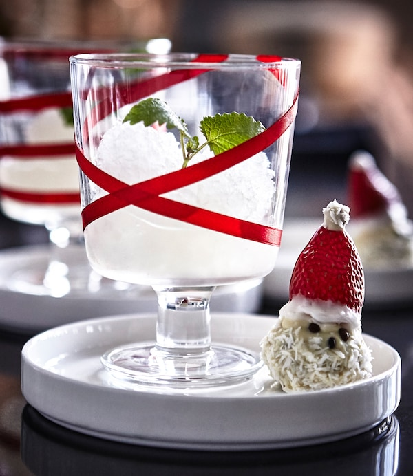 An IKEA 365+ wine glass decorated with red ribbon and filled with a granita, next to a treat shaped like a snowman.