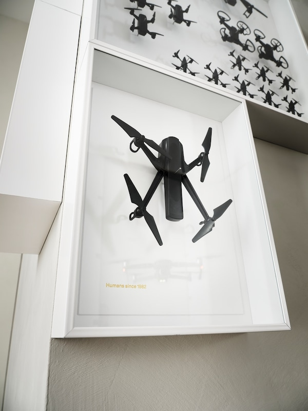 An IKEA ART EVENT 2021 wall piece with a black drone in a white frame; a second wall piece with drones is above it.