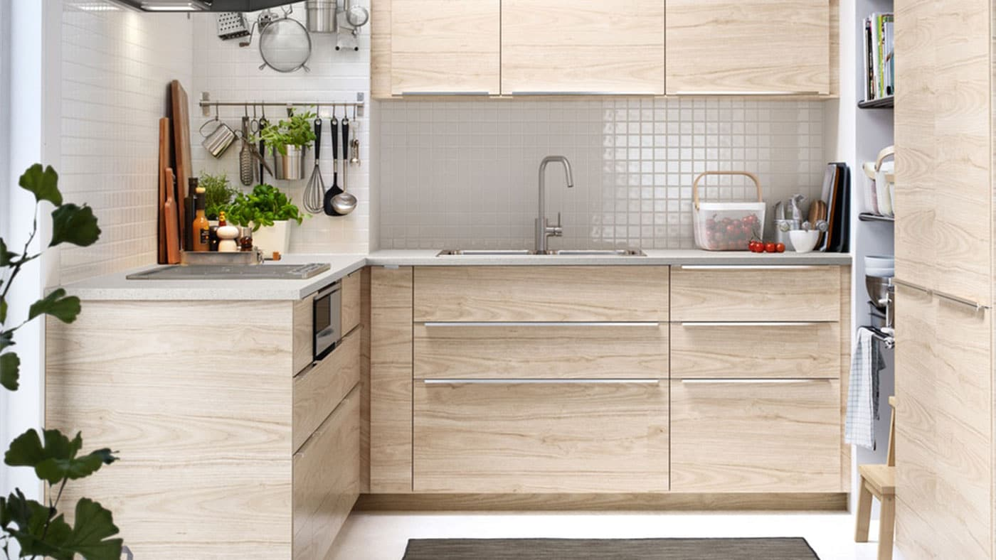 An IKEA ASKERSUND kitchen with wooden worktop and metal, slimline handles.