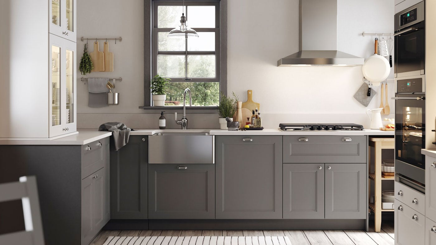 An IKEA AXSTAD grey kitchen with white worktop, metal handles and door knobs.