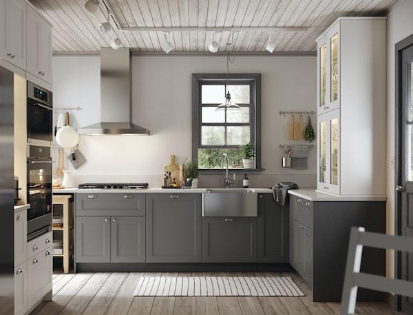 An IKEA AXSTAD grey kitchen with white worktop, metal handles and door knobs.