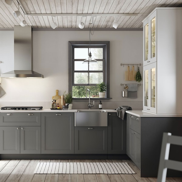 An IKEA AXSTAD kitchen with grey lower units and white cabinets.