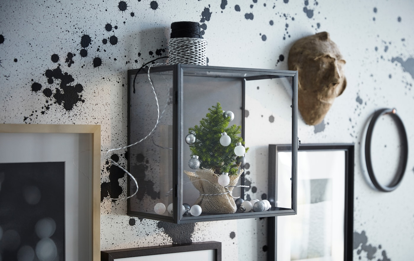 An IKEA BARKHYTTAN display box on a wall, containing a miniature tree with baubles, alongside picture frames.