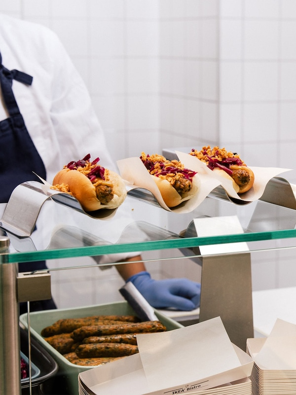 An IKEA bistro barista is standing behind the counter that has three veggie hot dogs placed on the till on a wavy metal hot dog stand.