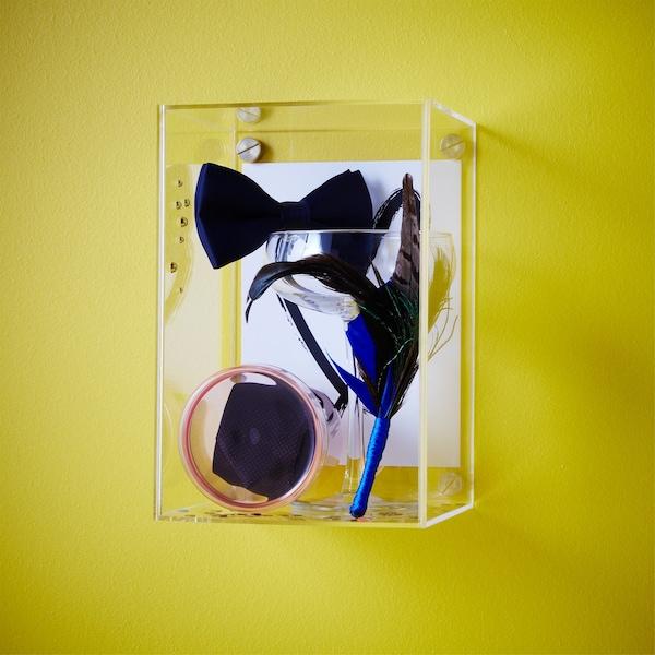 An IKEA BJÖRNARP acrylic display box filled with wedding souvenirs.