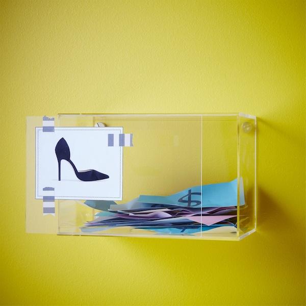 An IKEA BJÖRNARP acrylic display box on the wall with a shoe sketch pinned to the front and pretend money inside.