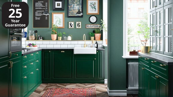 An IKEA BODBYN dark green kitchen with black worktop and traditional, golden door handles.