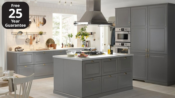 An IKEA BODBYN grey kitchen with white worktop and small, golden door knobs.