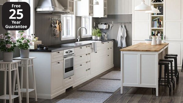 An IKEA BODBYN off-white kitchen with dark grey worktop and small, round door knobs.