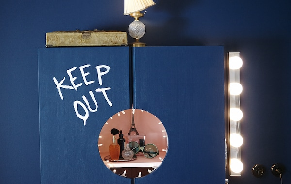 "An IKEA cabinet is turned into a vanity. The words ""Keep out"" are painted on the front, a circle has been but from the doors for a view of the interior."
