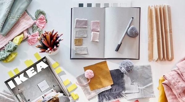 An IKEA catalogue, planning journal, and fabric swatches ontop of a white table.