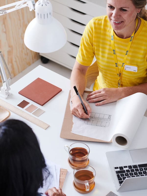 An IKEA co-worker in a yellow top talking to a customer, writing down notes on a plan on a work desk with a white lamp.