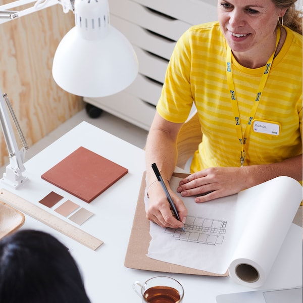 An IKEA co-worker in yellow sitting with a customer drawing plans on a pad of paper.