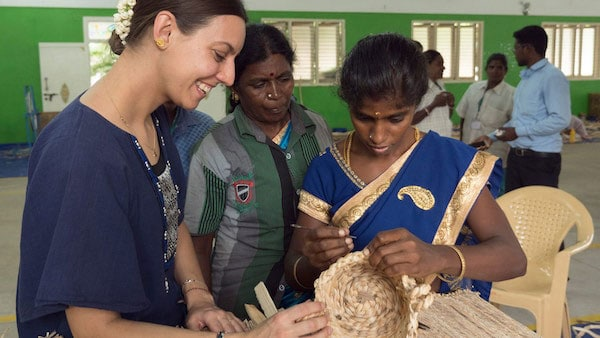An IKEA designer with Indian artisans looking together at a handwoven basket talking about the weaving technique.