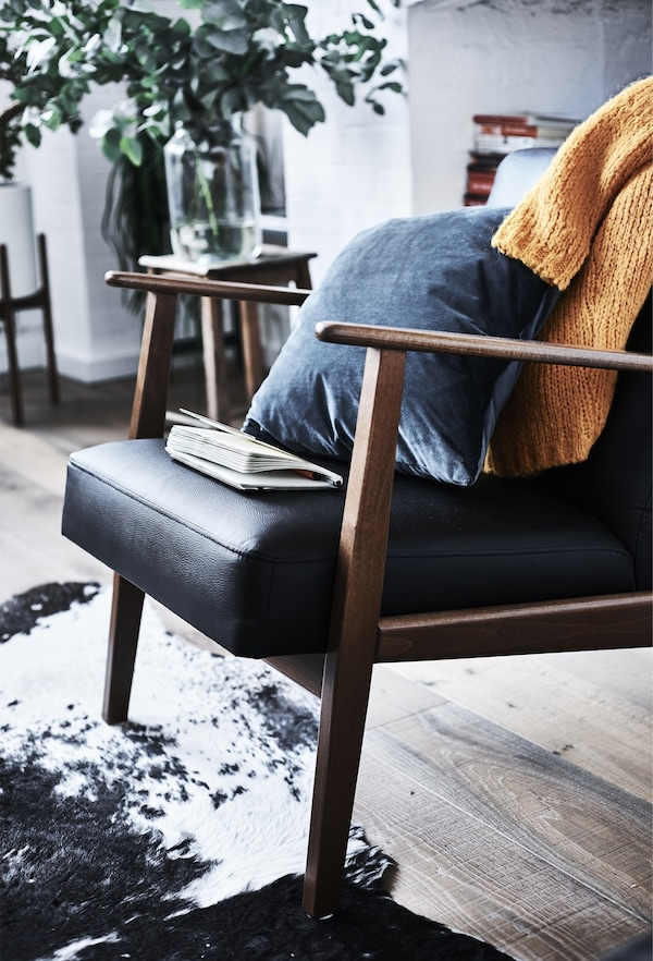 An IKEA EKENÄSET armchair, with a blue cushion and an orange jumper across the backrest.