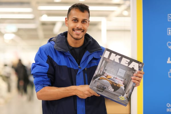 An IKEA Family member holding his IKEA Coffee Table Catalogue
